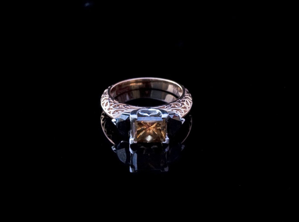 Overhead view of the White Gold Cognac Diamond Ring, with the head of the ring pointed towards camera. Cushion cut cognac diamond held in the center with 2 shield cut black diamonds on either side.