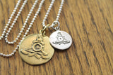 Large brass naval seal pendant and smaller silver naval seal pendant on a silver chain