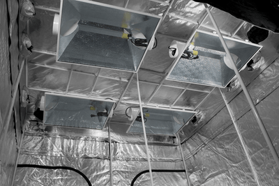 reflective interior ceiling of large grow tent, with white steel poles and exhaust ducts cinched with black drawstring