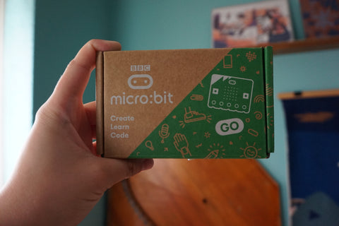 hand holding the micro:bit box in the air