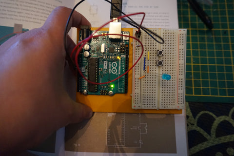 Hand holding the mounted Arduino and breadboard showing a parallel circuit