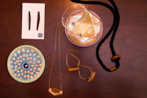 selection of jewelry laid out on table with other objects