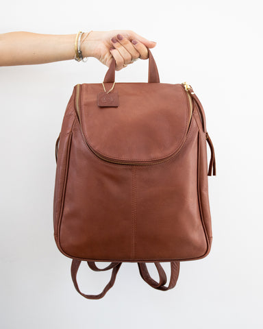 hand holding nora backpack in brandy