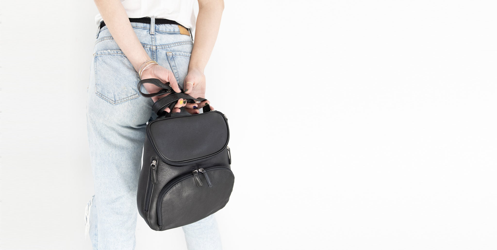 woman holding leather backpack