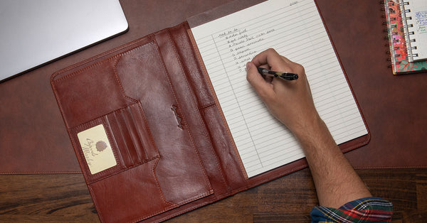 hand writing on paper in leather portfolio