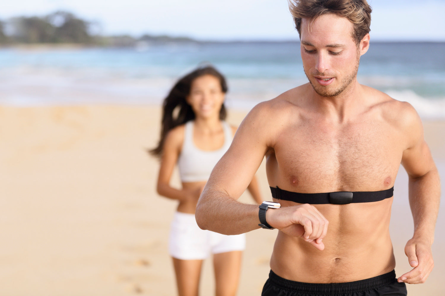 couple running on beach with heart rate monitor