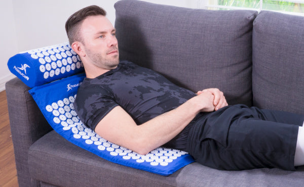 Man lying on ProsourceFit Acupressure Mat