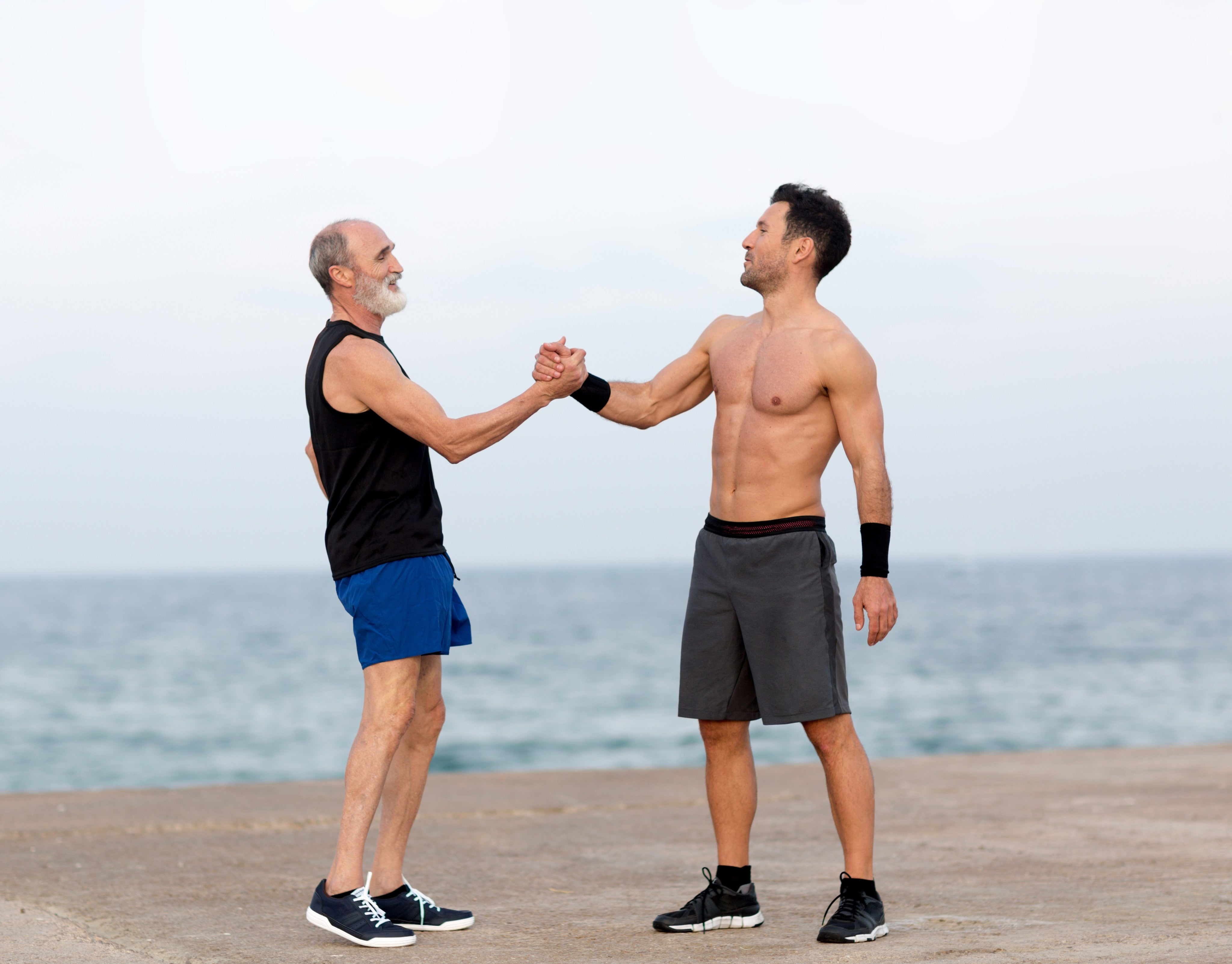 Father and son grasping hands on beach