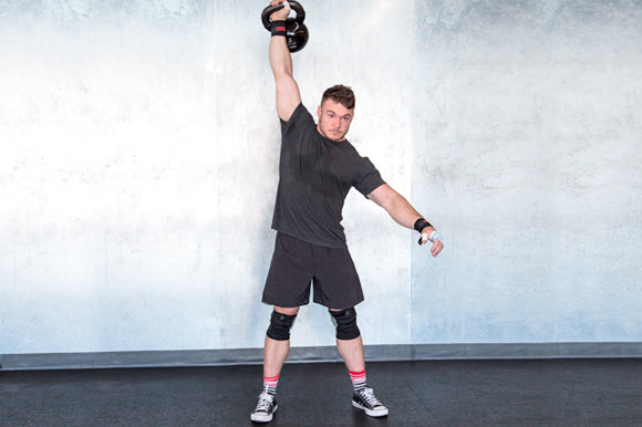 Fit man doing kettlebell snatches with cast iron kettlebell