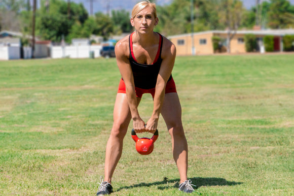 Fit woman doing kettlebell swings with ProsourceFit Vinyl Coated Cast Iron Kettlebell