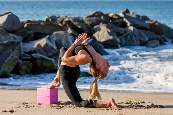 Woman doing yoga on beach with ProsourceFit pink foam yoga blacks