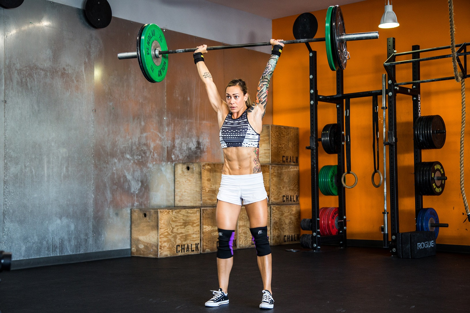 Woman doing Olympic lift at CrossFit box with prosource equipment