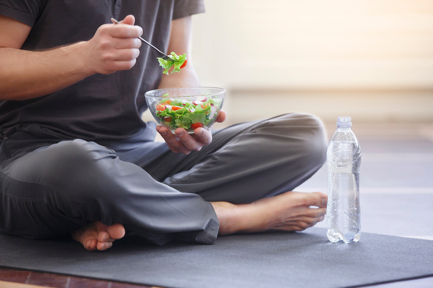 man eating salad on yoga mat
