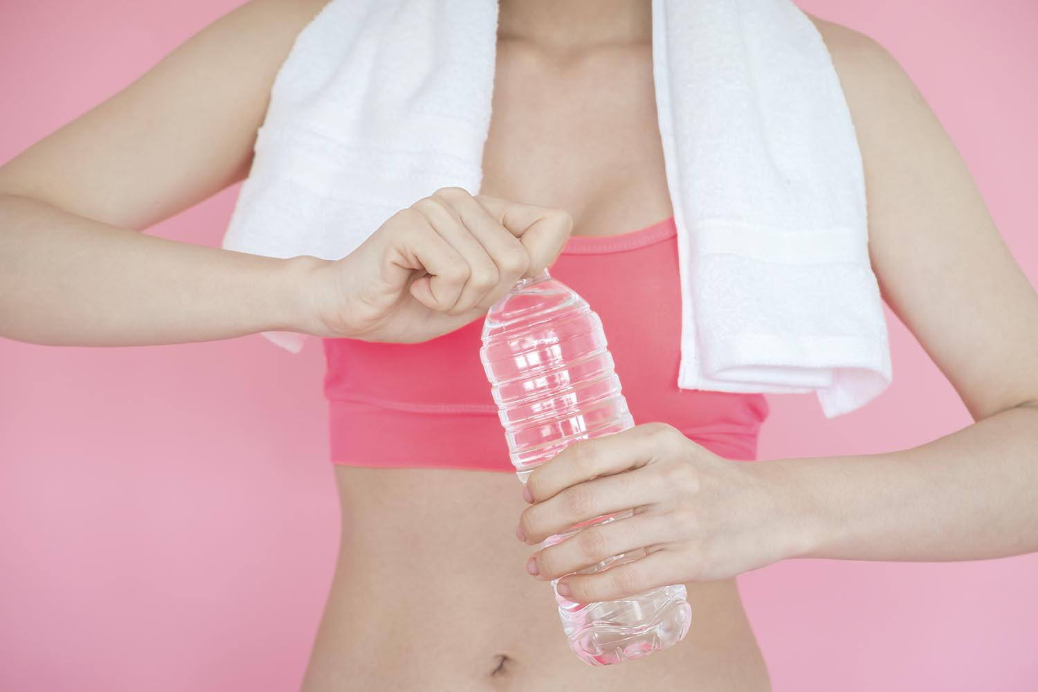 Woman holding water bottle pink background