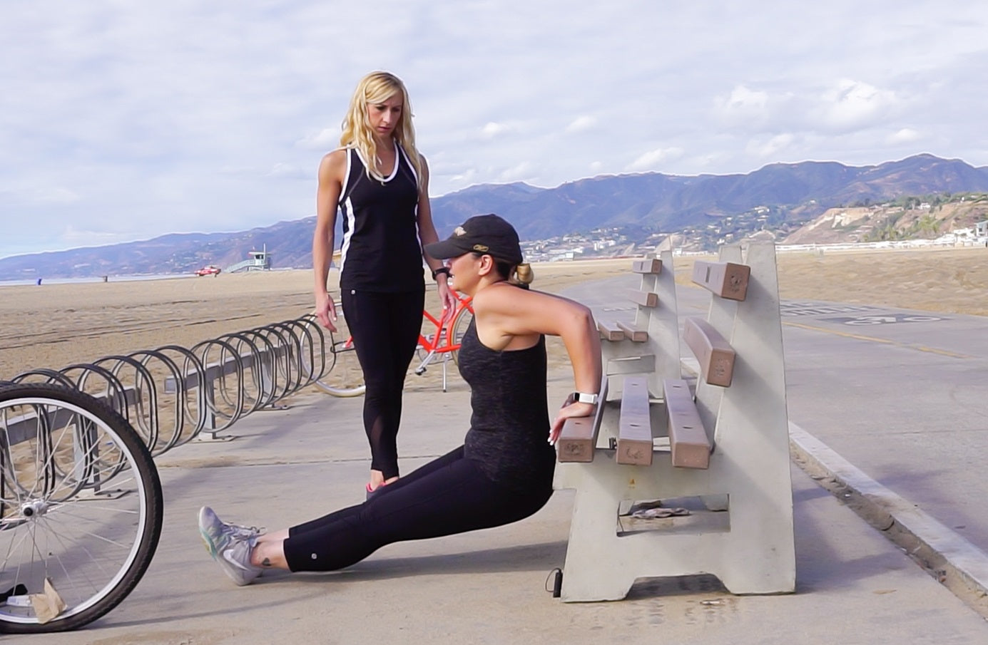 Woman and her personal trainer doing triceps dips on a bench at the beach