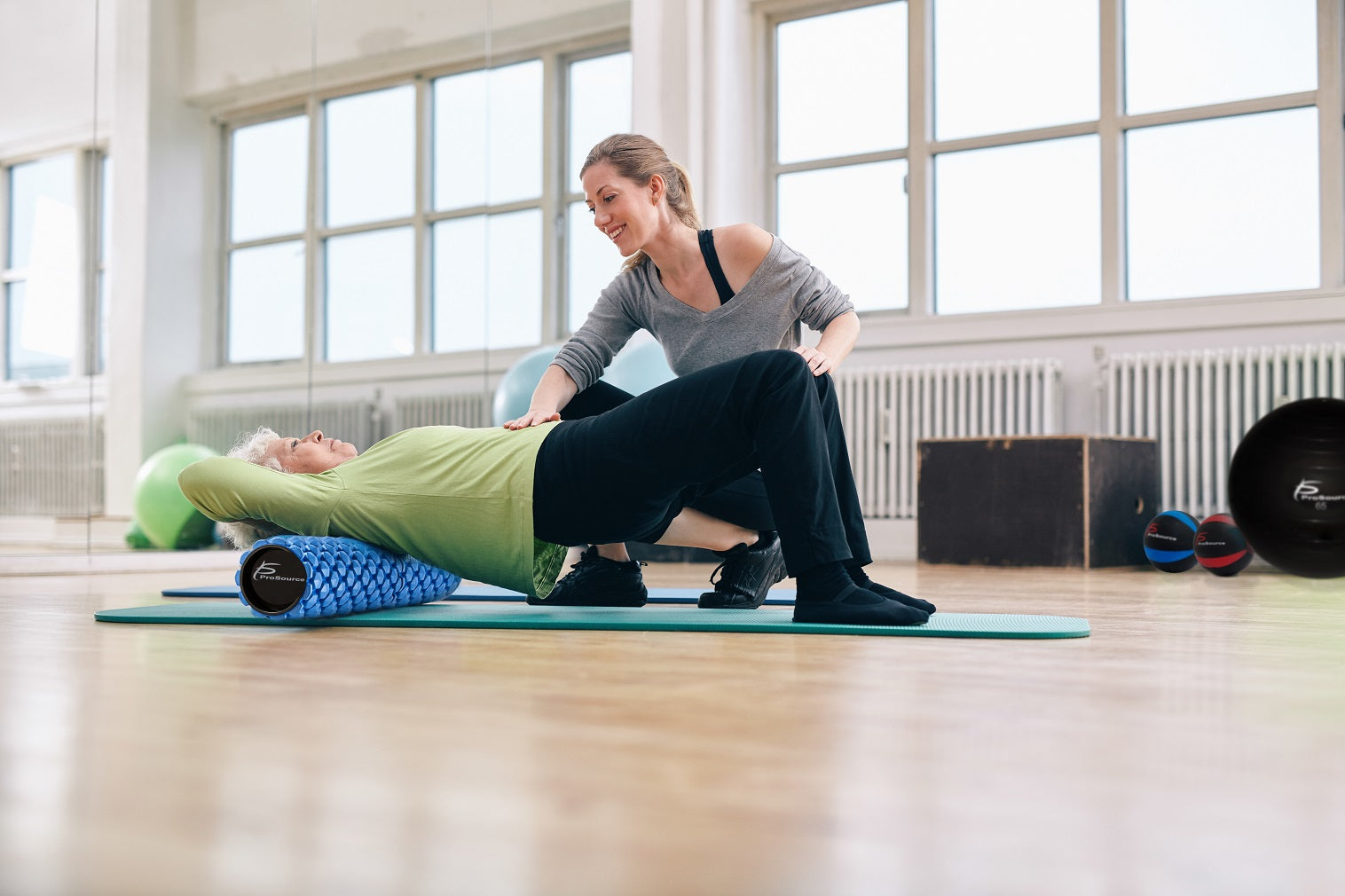 elderly woman stretching on prosource hexa 2-in-1 foam roller with her trainer