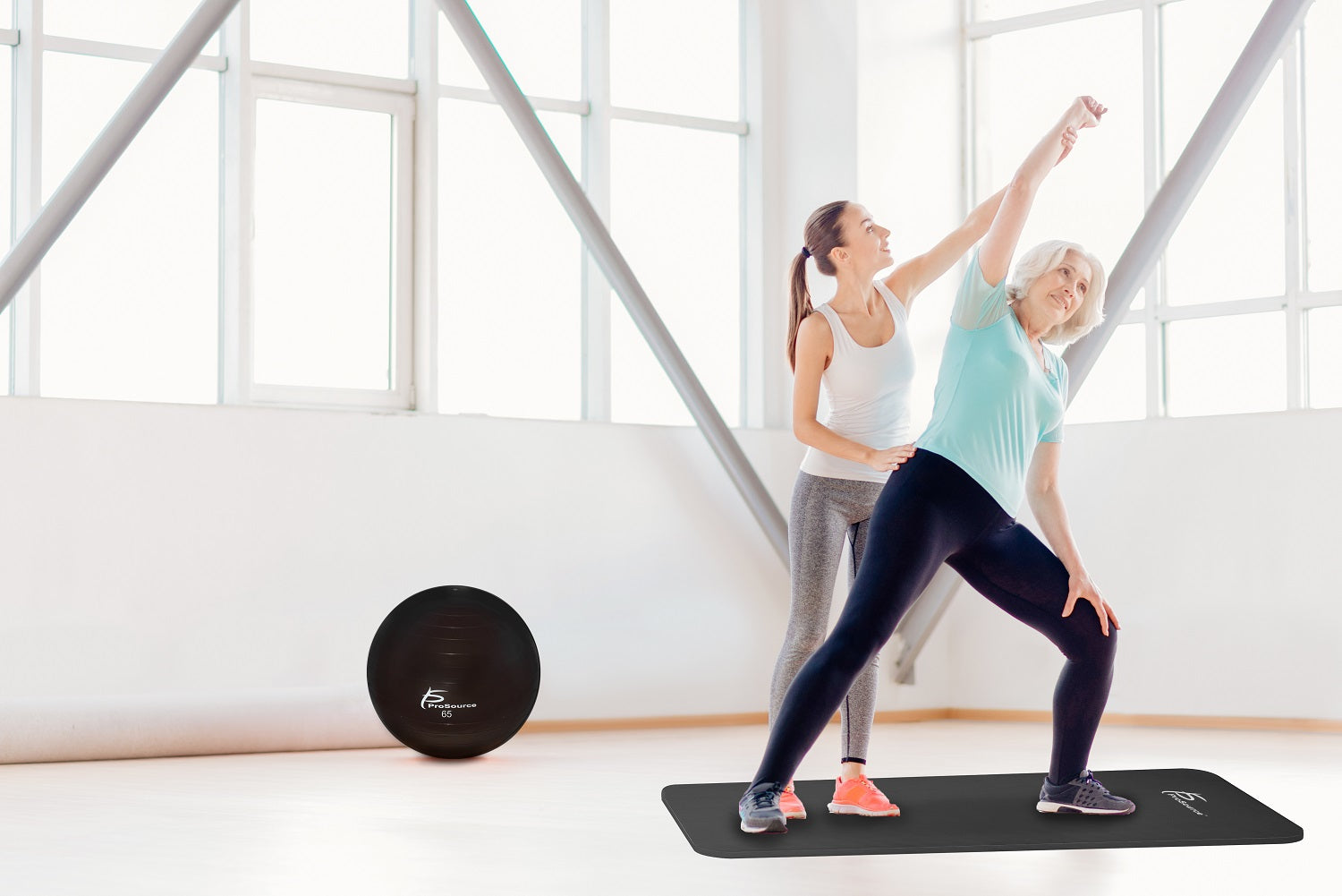 Elderly woman stretching on prosource extra thick yoga mat with trainer