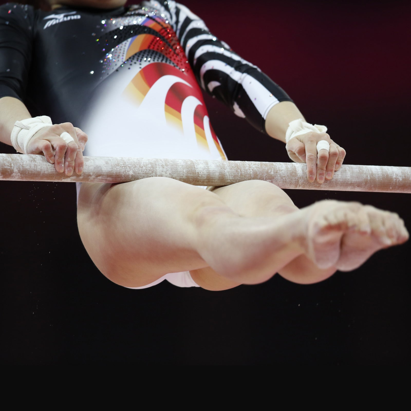 female gymnast performing toes to bar exercise