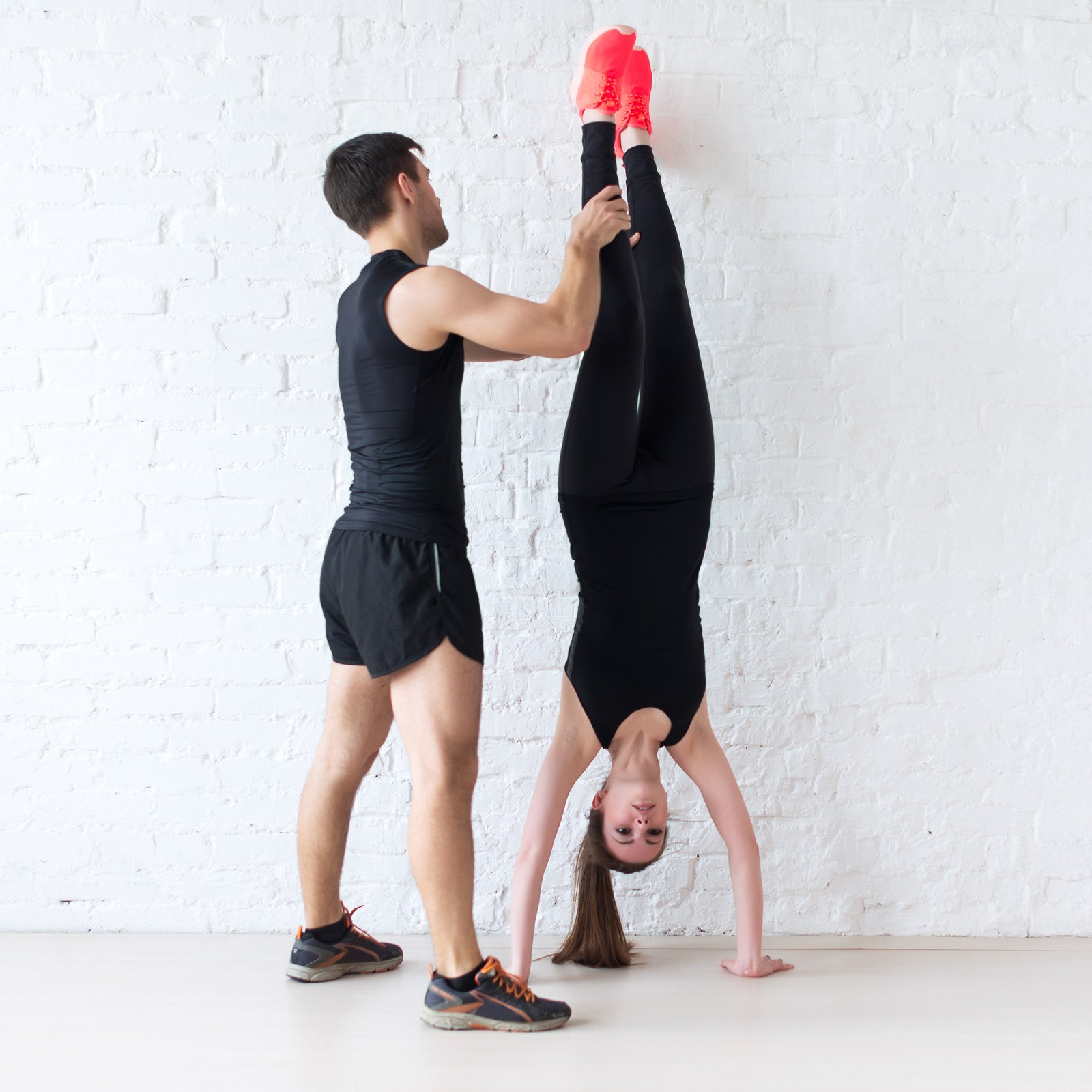 man assisting woman into handstand