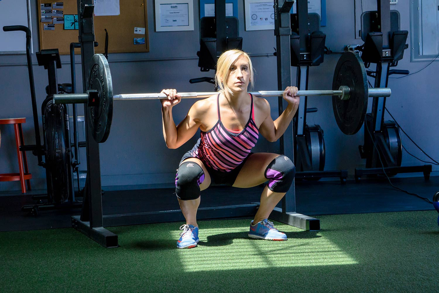 Fit woman using Woman using ProsourceFit barbell, bumper plates and knee sleeves while in a barbell squat