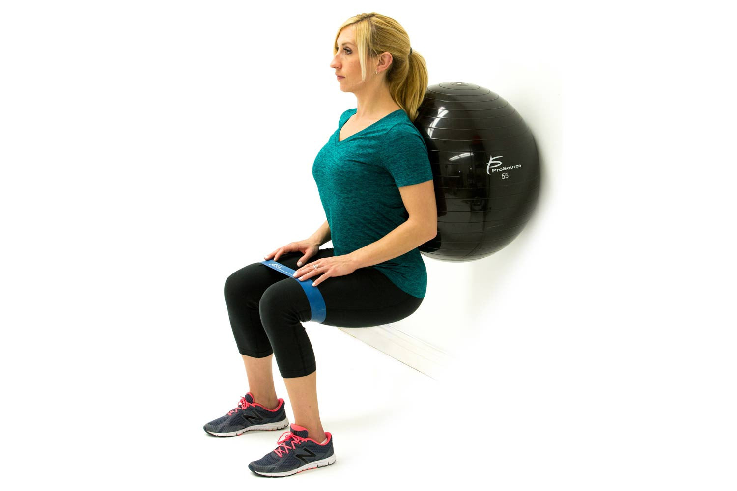 Woman doing ball squats with ProsourceFit loop resistance bands and stability ball