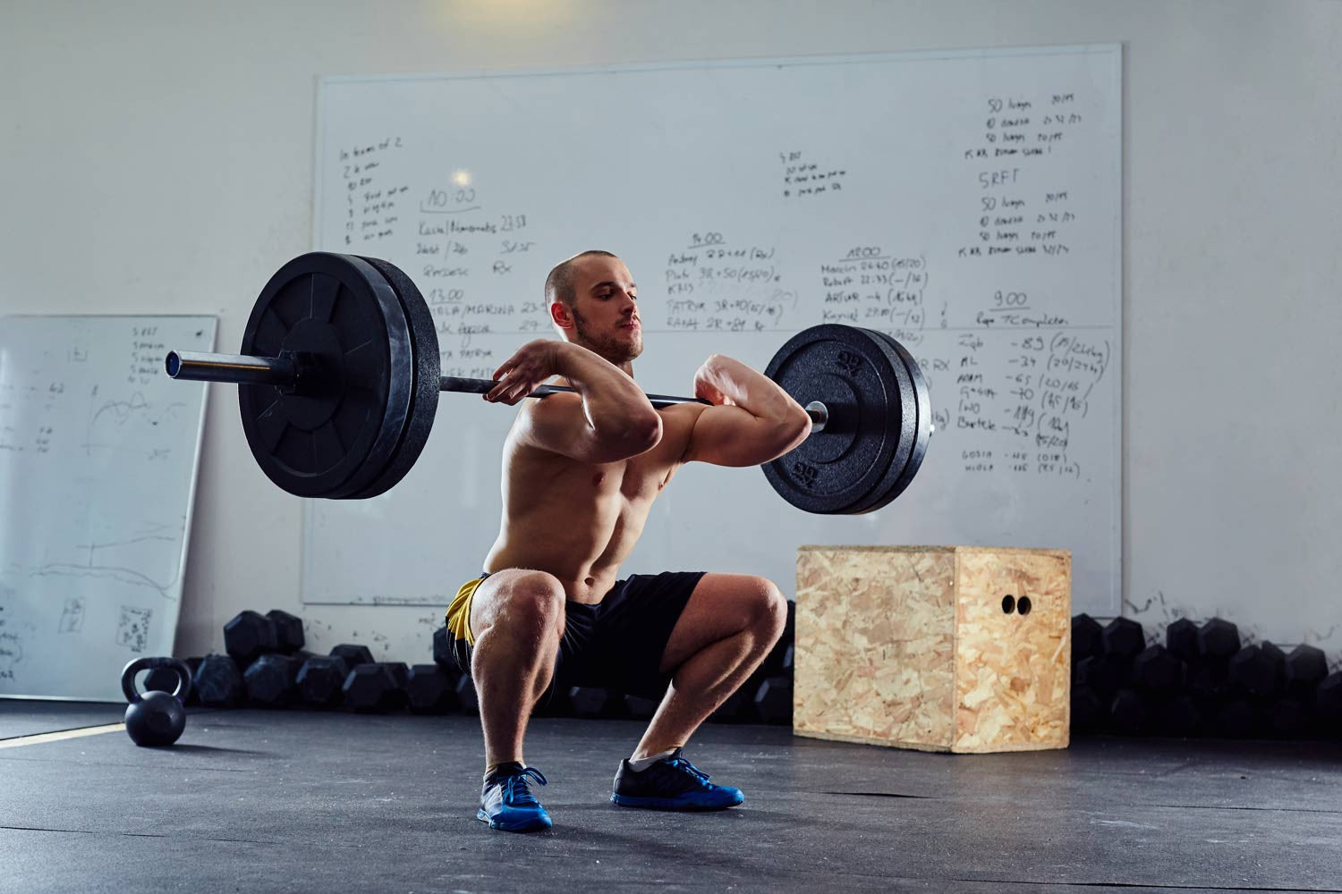 Man squatting with barbell and bumper plates