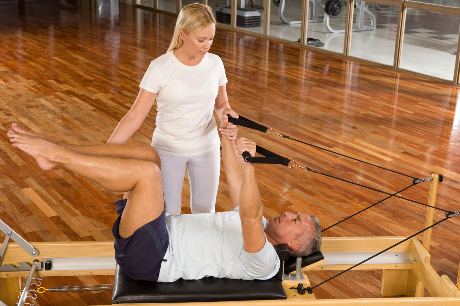 Man doing pilates on a reformer with woman teacher
