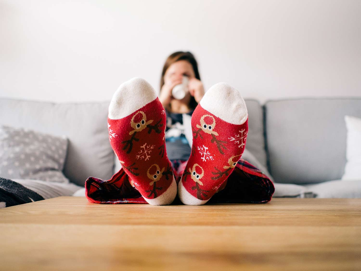 woman wearing red christmas socks with feet on coffee table