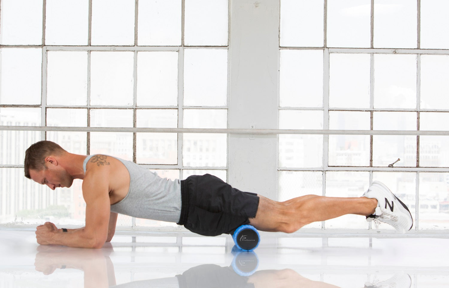 Man using a ProSource 2-in-1 Hexa Massage Roller for self-myofascial release on his thighs