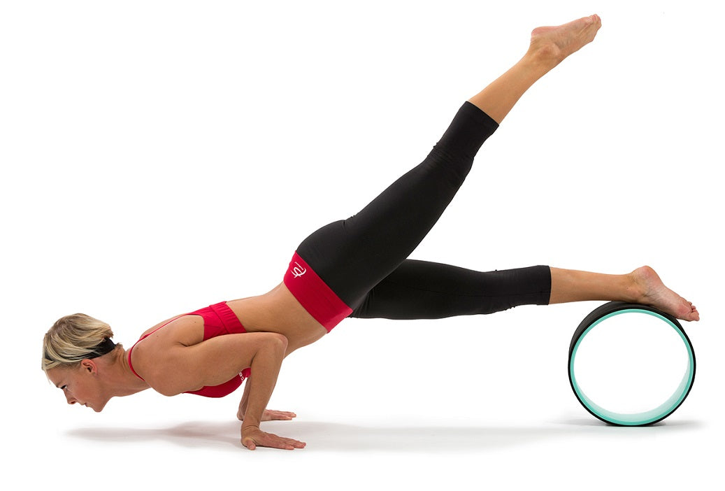Woman doing peacock pose on ProSource yoga wheel