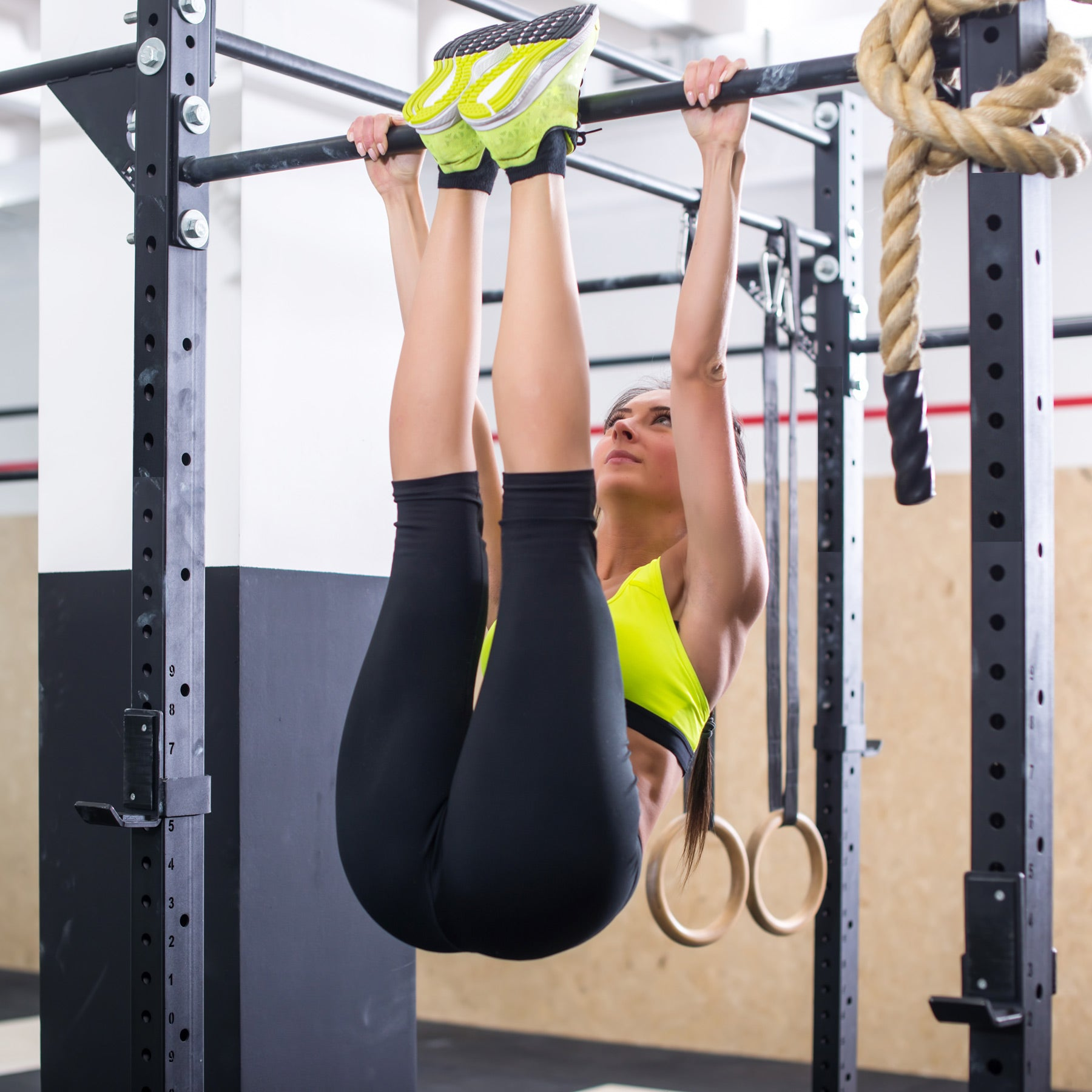 woman practicing toes to bar exercise in gym