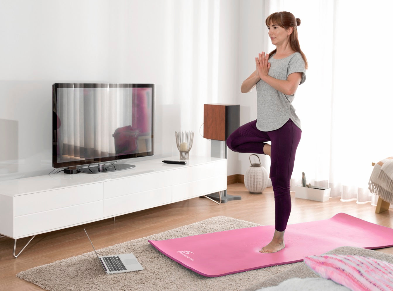 Woman doing online yoga at home