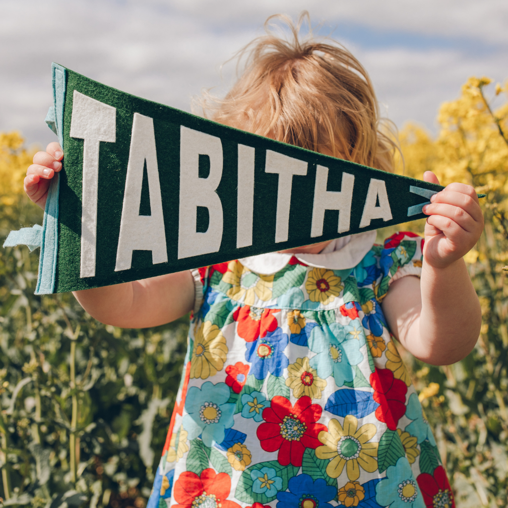 Child holding Personalised Name Pennant