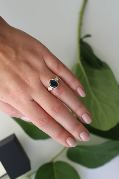 Deep blue sapphire oval sun ring with pear shaped diamond accents in 14 k yellow gold
