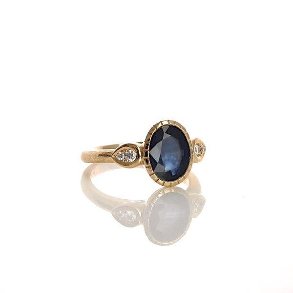 Deep blue sapphire sun ring with pear shaped diamond accents in 14 k yellow gold