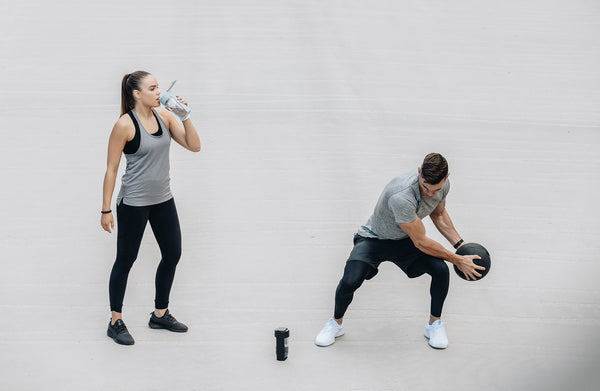 two people exercising drinking water