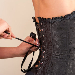 Waist training corsets fitting onto client