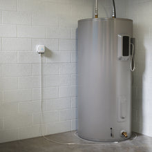 Load image into Gallery viewer, SensXtend by LeakSmart Kit product image showing the LeakSmart Water Sensor Dock mounted on a basement wall with LeakSmart Rope Water Sensors extending and wraping arounfd the base of the hot water tank.