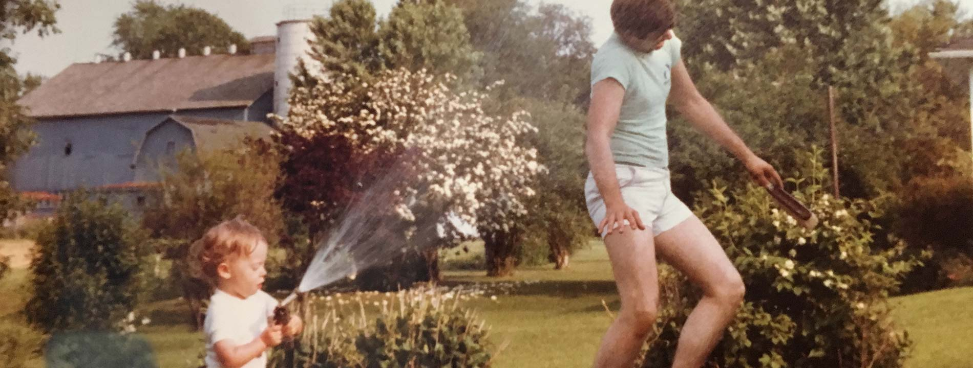 Young Ryan Martin spraying his dad with a water hose
