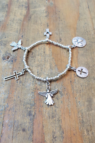 Bali Queen Wholesale silver rhodium based stretchy alloy metal Cross and Angel charm bracelet.  Made in Bali, Hypoallergenic, Tarnish resistant. Vegan.
