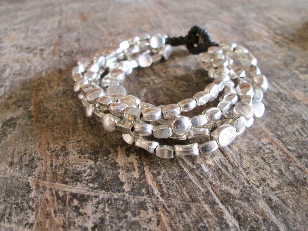 Bali Queen Wholesale silver Rhodium based alloy metal 5 strand oval on waxed lined cord. Made in Bali, Hypoallergenic, Tarnish resistant. 5 strands of silver beads. Rhodium based alloy metal on waxed linen cord. Button closure.
