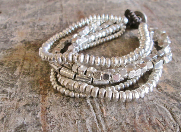 Bali Queen brand Rhodium Alloy bracelets on waxed linen cord. Hypoallergenic, tarnish resistant. Made in Bali. 6 strand Alloy bracelet. Button closure.