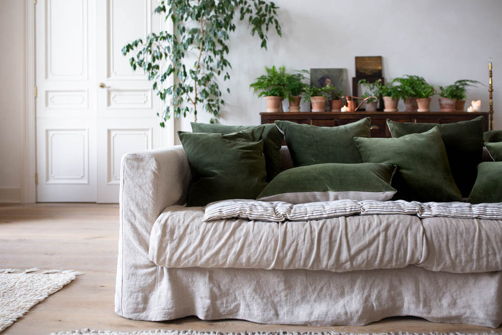 natural linen sofa with green velvet cushions