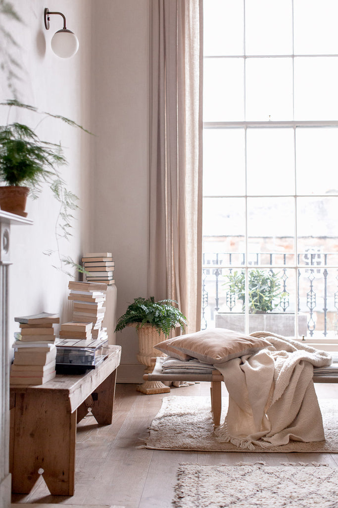 daybed surrounded by books by a big window