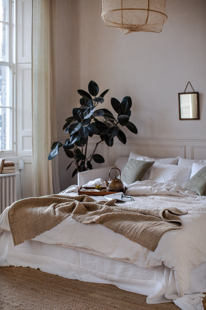 Natural bedroom decor with plants, linen and wool