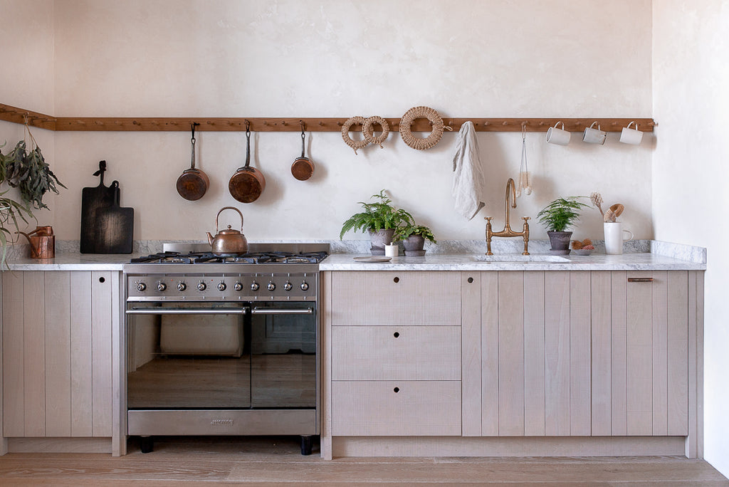 natural wooden kitchen with venetian plaster walls, brass, copper, marble and potted plants