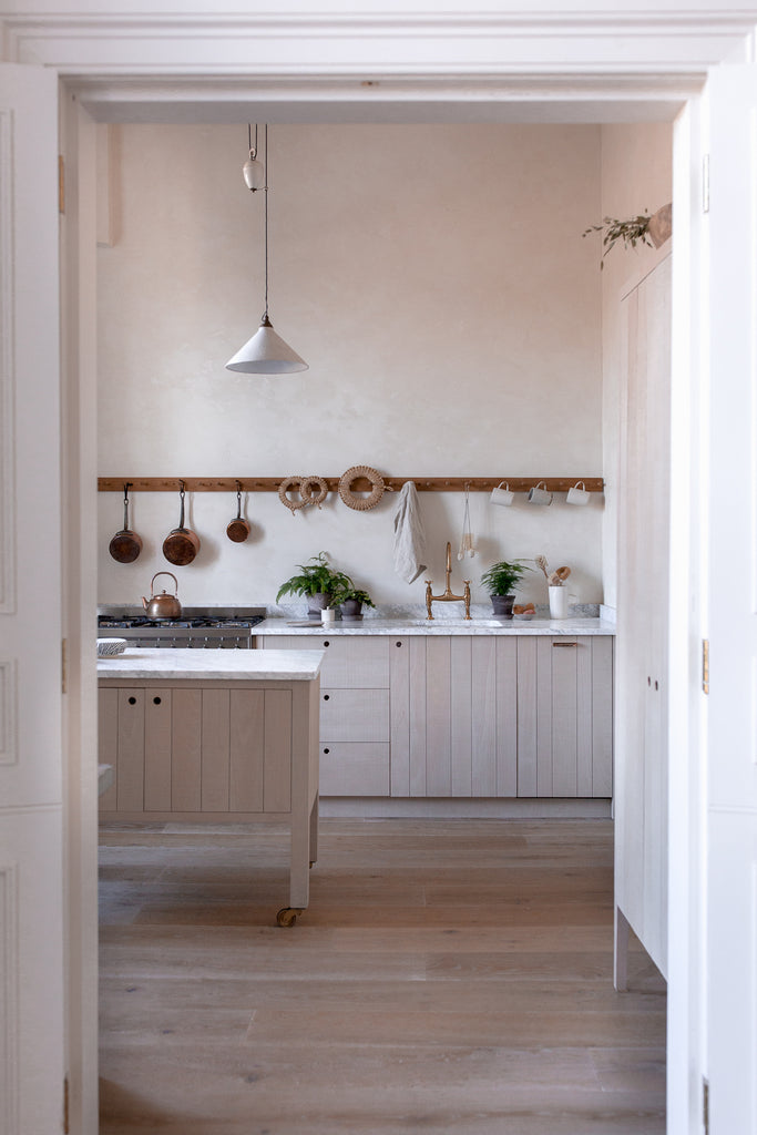 natural wood kitchen with plaster walls marble work top peg rail and kitchen island on wheels