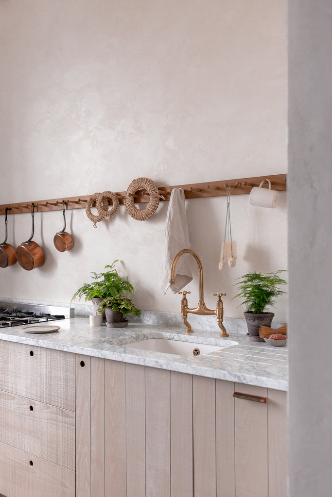 natural wood kitchen with marble work copper brass and plants