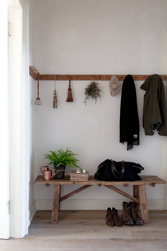 hallway with vintage wooden bench coat hooks