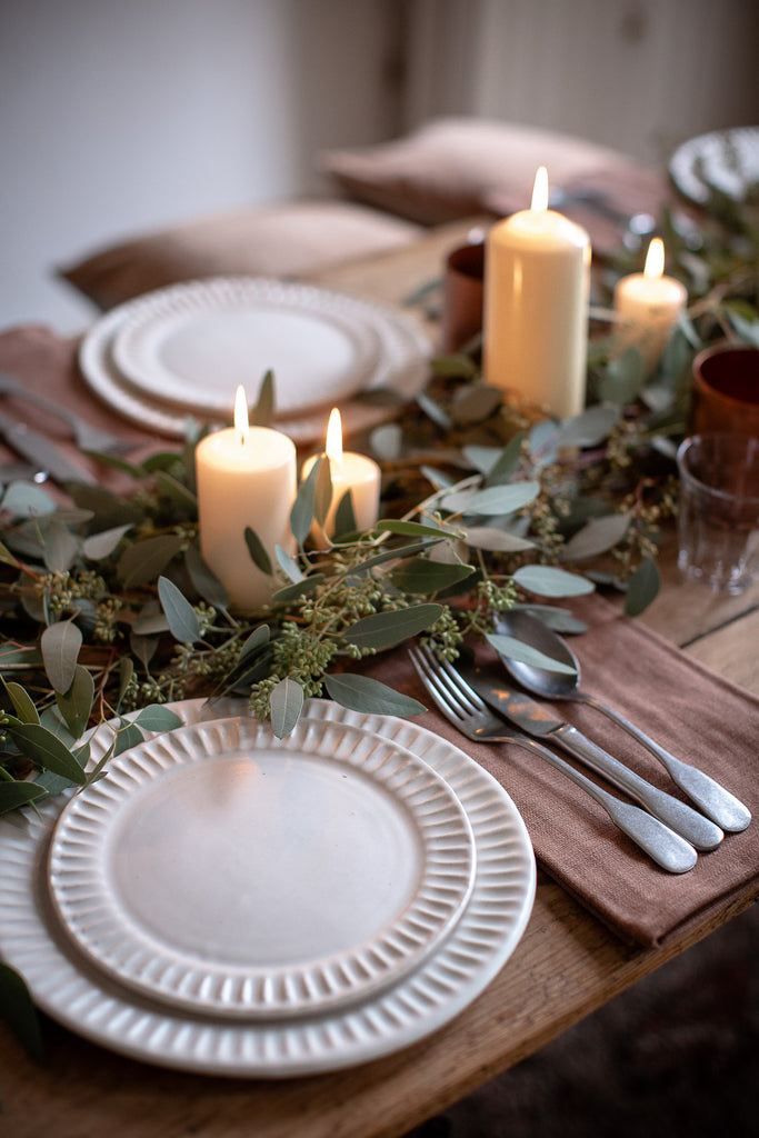 simple table decor with handmade plates, candles and eucalyptus